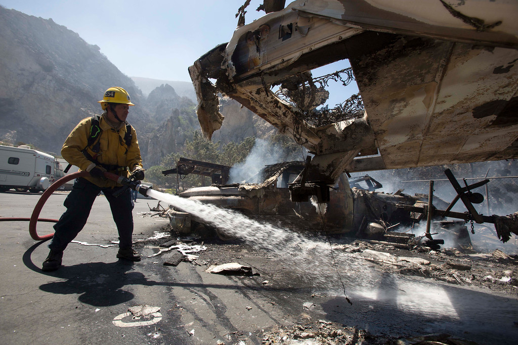 . A firefighter puts out a fire while the mobile homes are burning after after a blaze broke out during morning rush hour along U.S. 101 in the Camarillo area about 50 miles west of Los Angeles, May. 2, 2013, in Camarillo, Calif.  (AP Photo/Ringo H.W. Chiu)
