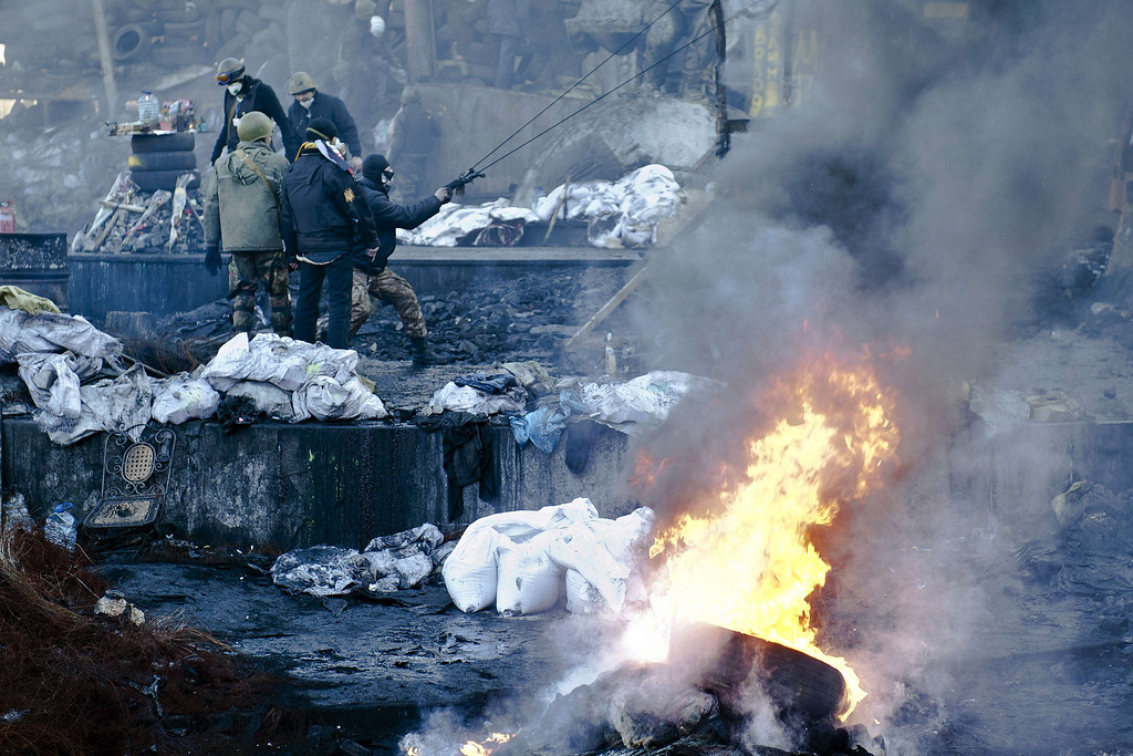 """. Opposition demonstrators stand on a barricade during clashes with police in Kiev on February 18, 2014. Opposition leader Vitali Klitschko on Tuesday urged women and children to leave the opposition\'s main protest camp on Kiev\'s Independence Square, known as Maidan, as riot police massed nearby. \""""We ask women and children to quit Maidan as we cannot rule out the possibility that they will storm (the camp),\"""" the former heavyweight boxing champion told protestors on the square.  AFP PHOTO / PIERO QUARANTA/AFP/Getty Images"""