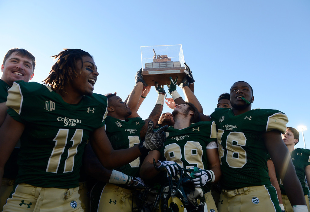 . The Colorado State Rams football team hoist the AFROTC DET. 90 Ram-Falcon trophy to celebrate their victory over the Air Force Falcons with the fans Saturday afternoon, November 30, 2013. The Rams won 58-13. (Photo By Andy Cross/The Denver Post)