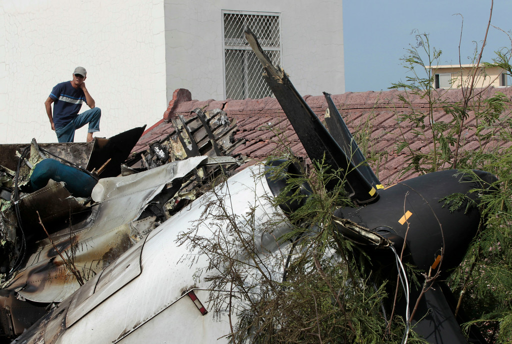 . A local resident watches the forensic investigation among the wreckage of crashed TransAsia Airways flight GE222 on the outlying island of Penghu, Taiwan, Thursday, July 24, 2014.  (AP Photo/Wally Santana)