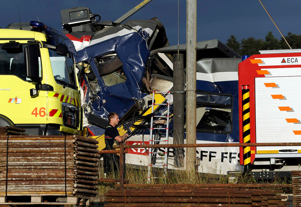 . A rescue worker stands near two Swiss regional trains after a head-on collision near Granges-Pres-Marnand near Payerne in western Switzerland July 29, 2013. The two trains collided in the Swiss canton of Vaud on Monday evening, injuring about 40 people, four seriously, Swiss news agency ATS reported. There was no immediate report of any deaths in the crash.  REUTERS/Denis Balibouse