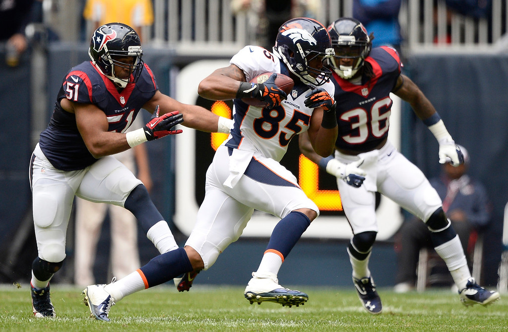 . Denver Broncos tight end Virgil Green (85) picks up a big gain as Houston Texans inside linebacker Darryl Sharpton (51) and Houston Texans strong safety D.J. Swearinger (36) move in on defense during the first quarter December 22, 2013 at Reliant Stadium. (Photo by John Leyba/The Denver Post)