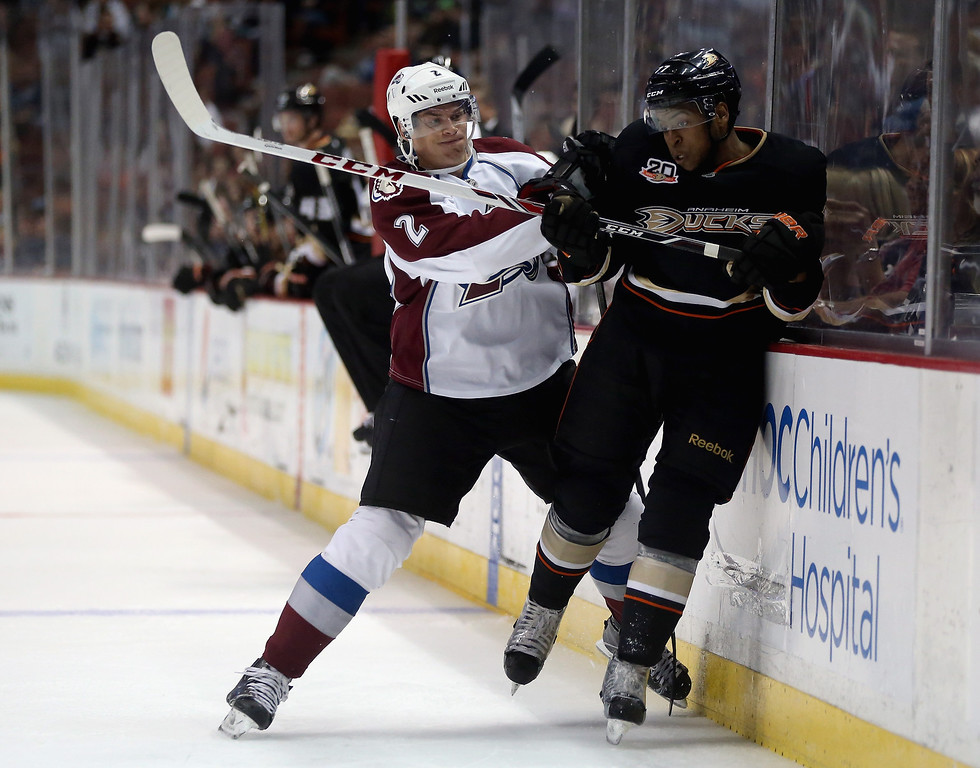 . Nick Holden #2 of the Colorado Avalanche checks Devante Smith-Pelly #77 of the Anaheim Ducks into the boards in the second period at Honda Center on September 22, 2013 in Anaheim, California.  (Photo by Jeff Gross/Getty Images)