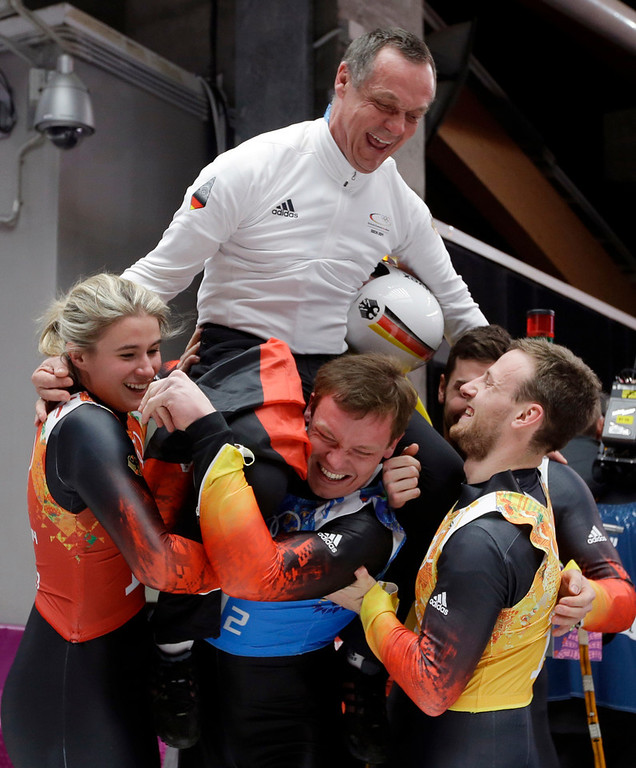 . The German team lift their coach Norbert Loch up after they won the gold medal during the luge team relay competition at the 2014 Winter Olympics, Thursday, Feb. 13, 2014, in Krasnaya Polyana, Russia. (AP Photo/Natacha Pisarenko)