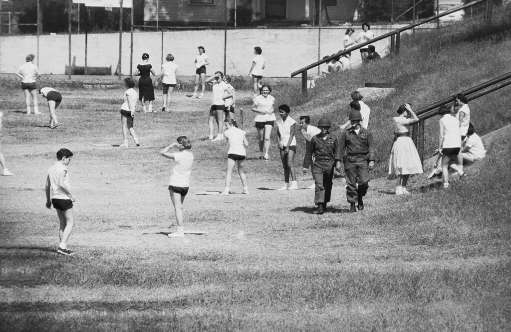 . Two soldiers stroll by as a group of Central High School girls, including one of the nine African American students Gloria Ray, hold outdoor gym exercises on Oct. 7, 1957. Two other soldiers, apparently assigned to guard the African American  student, waited with billy clubs at the entrance to the field. (AP Photo/FK)