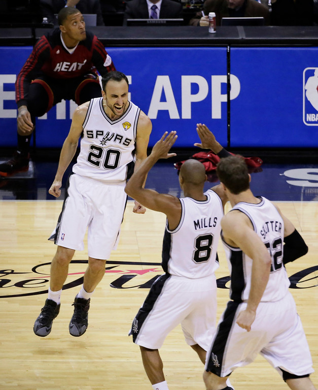 . San Antonio Spurs guard Manu Ginobili (20), guard Patty Mills (8) and center Tiago Splitter (22) celebrate against the Miami Heat during the second half in Game 5 of the NBA basketball finals on Sunday, June 15, 2014, in San Antonio. (AP Photo/Tony Gutierrez)