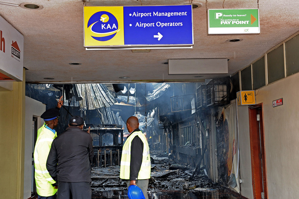 . Airport staff look at the debris after a fire damaged a terminal at the Jomo Kenyatta international airport in Nairobi on August 7, 2013. A massive fire shut down Nairobi\'s international airport on Wednesday with flights diverted to regional cities as firefighters battled to put out the blaze in east Africa\'s biggest transport hub. Dramatic plumes of black smoke billowed out of the main arrivals terminal, but by 9.00 am (0600GMT), some four hours after the blaze broke out, firefighters had succeeded in stemming the raging flames.  AFP PHOTO /StringerSTRINGER/AFP/Getty Images