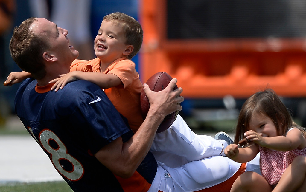 . Denver Broncos quarterback Peyton Manning (18) has a little fun with his son Marshall who tackles him and his daughter Mosley (R) after practice on day four of the Denver Broncos 2014 training camp July 27, 2014 at Sports Authority Field at Mile High. The kids came out to join him on the field after he signed autographs. (Photo by John Leyba/The Denver Post)