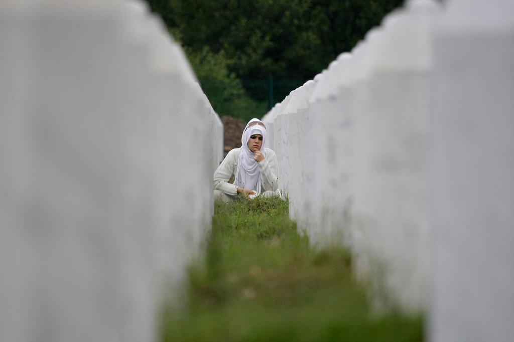 . Bosnian woman Zumreta Ahmetasevic prays amidst gravestones during a funeral ceremony at the memorial center in Potocari, near Srebrenica, 160 kms east of Sarajevo, Bosnia, Thursday, July 11, 2013. People from around Bosnia and abroad have begun arriving in Srebrenica Thursday to commemorate 18th anniversary of the 1995 massacre and rebury recently identified victims exhumed from mass graves. The victims\' bodies are still being exhumed from mass graves in the area, where Serbs had dumped them in an attempt to cover up the crime. Identified victims are buried each year on the massacre\'s anniversary at a memorial cemetery near Srebrenica.  (AP Photo/Amel Emric)