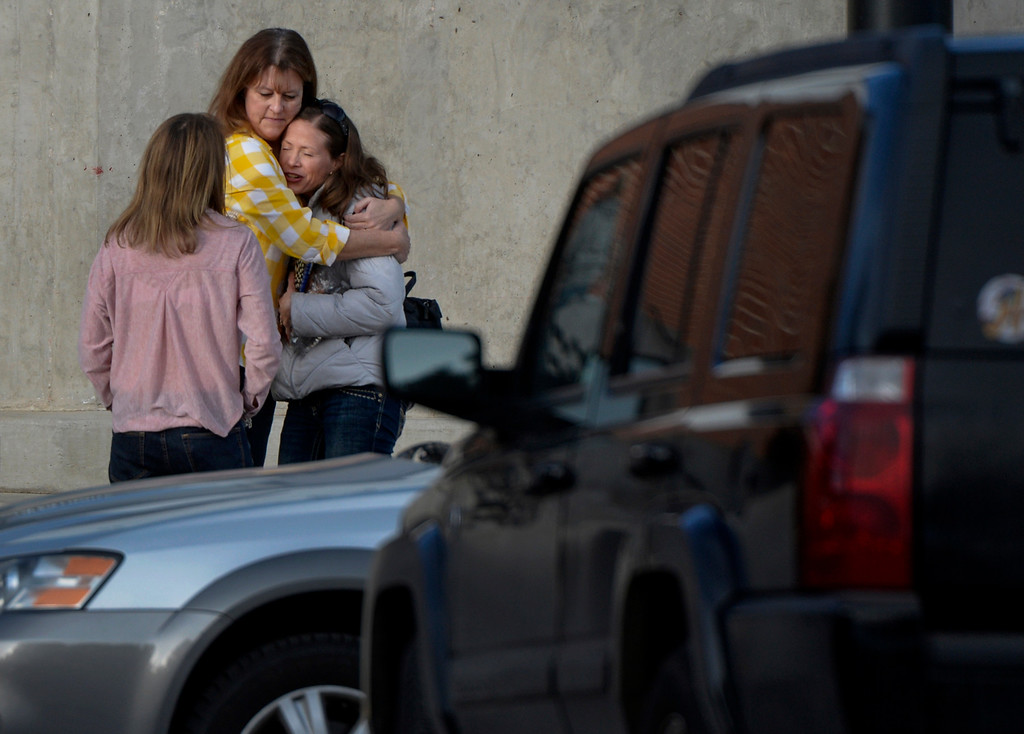 . Two women embrace outside the entrance to Arapahoe High School in Centennial, CO December 18, 2013. Faculty and staff were allowed to return to the school to retrieve belongings left in the building. (Photo By Craig F. Walker / The Denver Post)