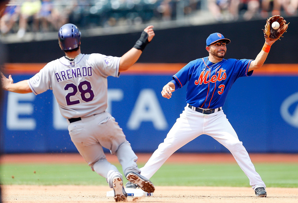 . Omar Quintanilla #3 of the New York Mets forces out Nolan Arenado #28 of the Colorado Rockies at second base during the seventh inning at Citi Field on August 8, 2013 in the Flushing neighborhood of the Queens borough of New York City. The Mets defeated the Rockies 2-1.  (Photo by Jim McIsaac/Getty Images)