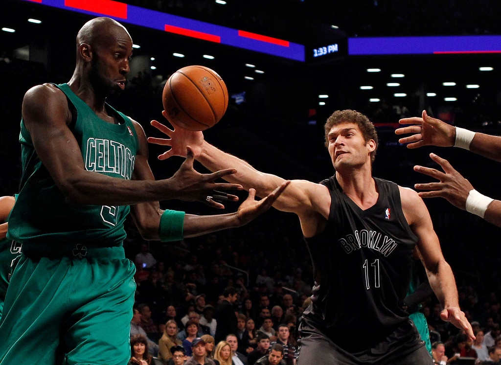 . Boston Celtics forward Kevin Garnett and Brooklyn Nets center Brook Lopez (R) fight for a loose ball in the third quarter of their NBA basketball game in New York, December 25, 2012.    REUTERS/Adam Hunger