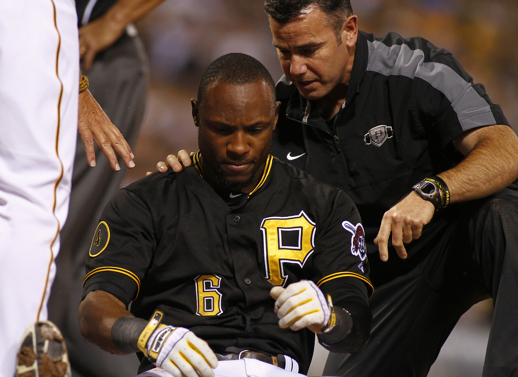 . PITTSBURGH, PA - JULY 18:  Athletic trainer Ben Potenziano tends to Starling Marte #6 after being hit in the head with a pitch in the seventh inning against the Colorado Rockies during the game at PNC Park July 18, 2014 in Pittsburgh, Pennsylvania.  (Photo by Justin K. Aller/Getty Images)