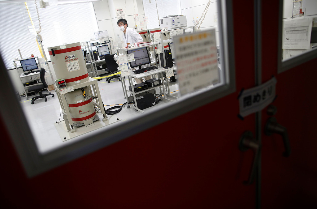 . A laboratory technician is seen through a closed door, as he tests for cesium levels in fish caught close to the Fukushima Daiichi nuclear plant, at Fukushima Agricultural Technology Centre in Koriyama, Fukushima prefecture May 28, 2013. Commercial fishing has been banned near the tsunami-crippled nuclear complex since the March 2011 tsunami and earthquake. The only fishing that still takes place is for contamination research, and is carried out by small-scale fishermen contracted by the government. Picture taken May 28, 2013. REUTERS/Issei Kato
