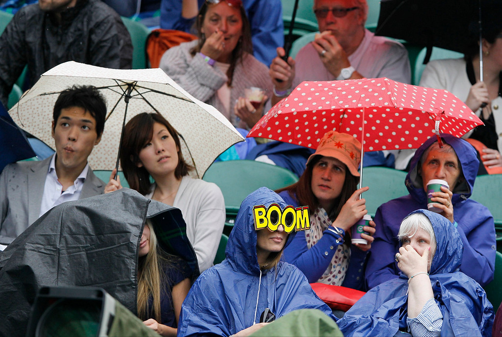 . Spectators seek shelter as rain delays play in a Women\'s singles quarterfinal match between Agnieszka Radwanska of Poland and Li Na of China at the All England Lawn Tennis Championships in Wimbledon, London, Tuesday, July 2, 2013. (AP Photo/Kirsty Wigglesworth)