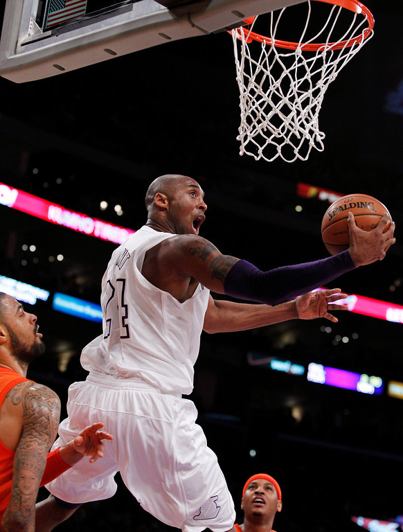 . Los Angeles Lakers guard Kobe Bryant (24) shoots a reverse lay up between New York Knicks center Tyson Chandler, left, and forward Carmelo Anthony, right, during the first half of their NBA basketball game in Los Angeles, Tuesday, Dec. 25, 2012. (AP Photo/Alex Gallardo)