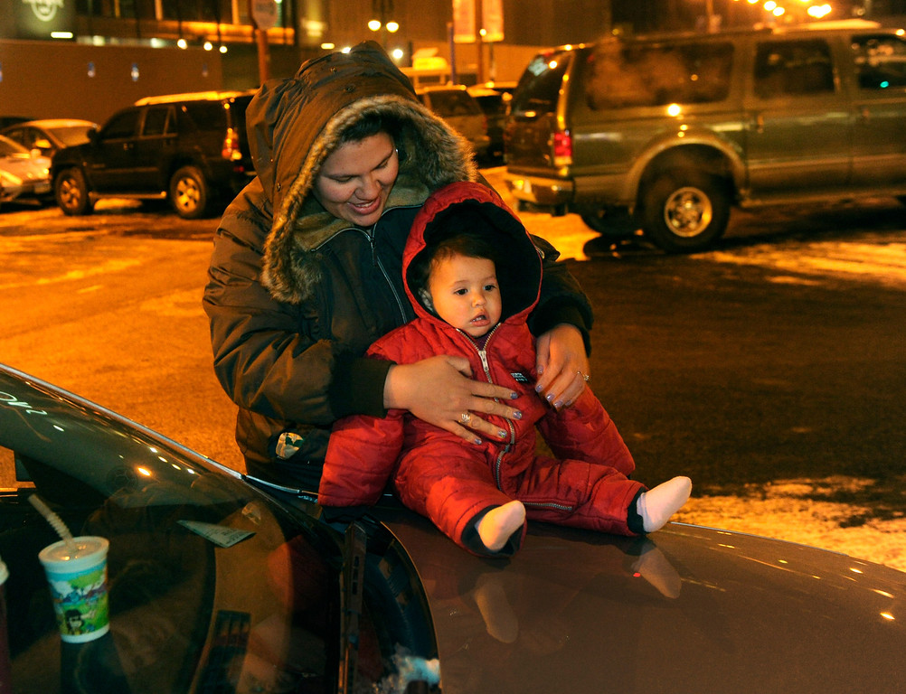 . DENVER, CO. - DECEMBER 06: Sarah Friedman zipped up the snowsuit for her one-year-old daughter Maya at the start of the 9News Parade of Lights Friday night, December 6, 2013. The weather was clear but temperatures dipped below zero. Photo By Karl Gehring/The Denver Post