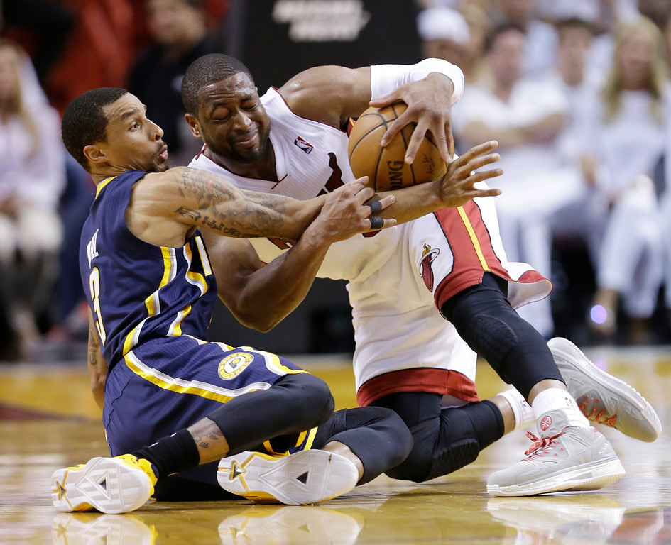 . Indiana Pacers guard George Hill (3) and Miami Heat guard Dwyane Wade (3), fight over a loose ball during the first half of Game 4 in the NBA basketball Eastern Conference finals playoff series, Monday, May 26, 2014, in Miami. (AP Photo/Wilfredo Lee)