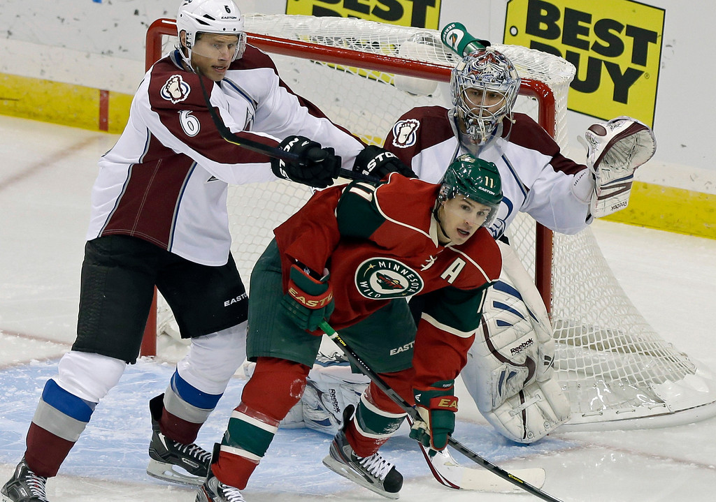 . Colorado Avalanche\'s Erik Johnson, left, tries to push Minnesota Wild\'s Zach Parise out of the way as Avalanche goalie Semyon Varlamov of Russia defends the net in the first period of an NHL hockey game Saturday, Jan. 19, 2013 in St. Paul, Minn. Parise and Ryan Suter signed identical 13-year, $98 million contracts with the WIld.  (AP Photo/Jim Mone)