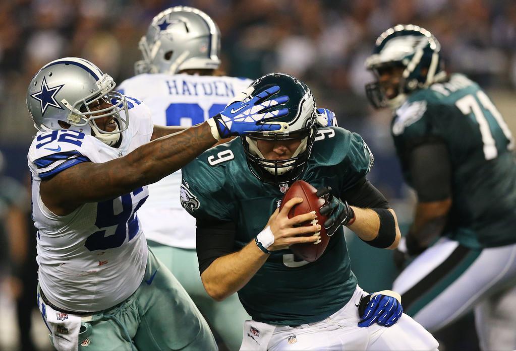 . Nick Foles #9 of the Philadelphia Eagles tries is tackled by Jason Hatcher #97 and Jarius Wynn #92 of the Dallas Cowboys in the first half at Cowboys Stadium on December 29, 2013 in Arlington, Texas.  (Photo by Ronald Martinez/Getty Images)