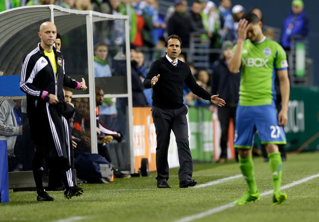 . Colorado Rapids head coach Oscar Pareja, center, reacts to a play that banged up Seattle Sounders\' Lamar Neagle, right, in the first half of a knockout-round match in the MLS Cup soccer playoffs Wednesday, Oct. 30, 2013, in Seattle. (AP Photo/Ted S. Warren)