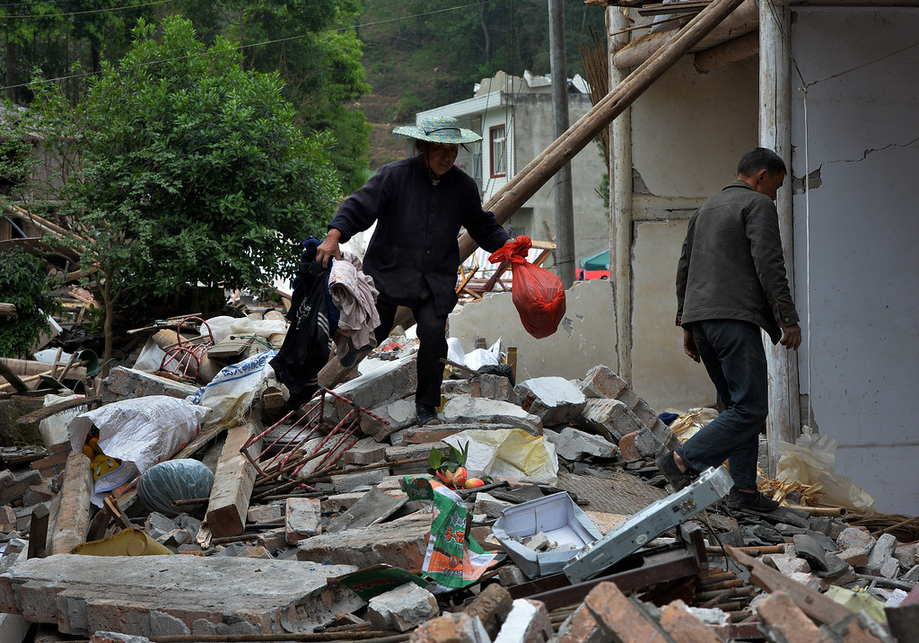 . Local residents search through rubble at their destroyed house near Longmen village after a magnitude 7.0 earthquake hit Lushan, Sichuan Province on April 22, 2013.    AFP PHOTO/Mark  RALSTON/AFP/Getty Images