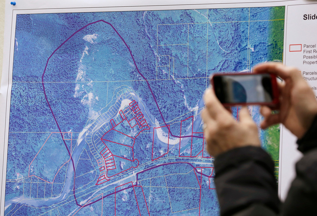 . A news person photographs a map showing the location of a deadly mudslide that happened two days earlier, before a news conference, Monday, March 24, 2014, in Arlington, Wash.  (AP Photo/Elaine Thompson)