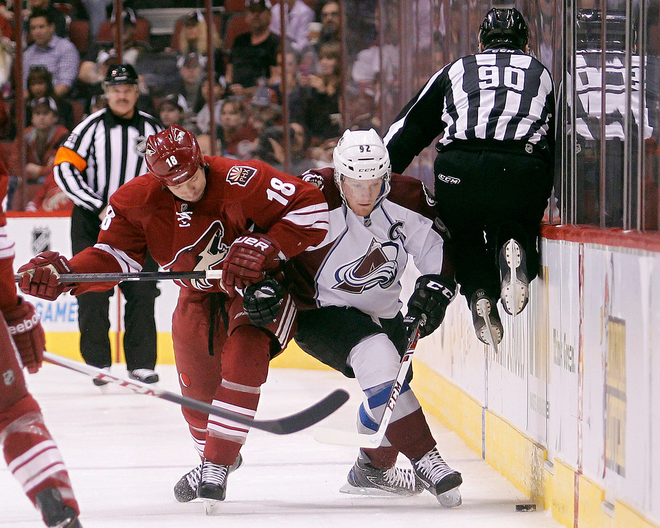 . Phoenix Coyotes right winger David Moss, left, battles Colorado Avalanche left winger Gabriel Landeskog, right, of Sweden, for the loose puck as linesman Andy McElman, right, leaps out of the way  in the first period of NHL hockey game, Saturday, April 6, 2013, in Glendale, Ariz. (AP Photo/Paul Connors)