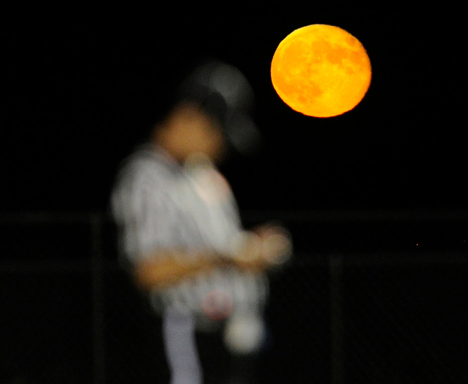 Description of . I was shooting the Holy Family High School football game against Silver Creek in Broomfield when I saw the full moon make an appearance in the sky.  The moon tends to look bigger the closer it is to the horizon but its fiery orange glow that night was no optical illusion.  During a break in the action I positioned myself to capture a referee taking notes as if he was using the light from the moon to better see his notepad.  This shot kind of sums up my nights in the fall when I'm out shooting so many football and soccer games in the increasingly cold autumn night.   BROOMFIELD, CO. - SEPTEMBER 20: The full moon rose to the east as the Holy Family High School football team hosted Silver Creek Friday night September 20, 2013.  (Photo By Karl Gehring/The Denver Post)