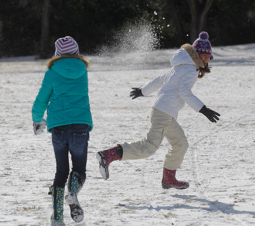 . Sofia Cabellero, 10, left, and Lauren Hecker, 10, of Fort Worth, have a snowball fight in Foster Park in Fort Worth, Texas, Wednesday, Dec. 26, 2012, after winter weather covered the area with layer of snow on Christmas Day. (AP Photo/The Fort Worth Star-Telegram, Rodger Mallison)