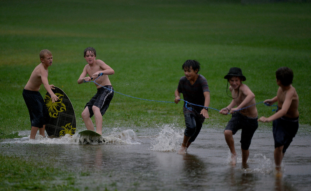 . BOULDER, CO. - SEPTEMBER12:  A group of youths use a flooded field for skimboarding at North Boulder Park in Boulder CO September 12, 2013. Record-breaking rain turned normally quiet creeks into raging, brown torrents that swept through Boulder on Thursday, flooding homes, swamping cars and closing roads and schools. (Photo By Craig F. Walker / The Denver Post)