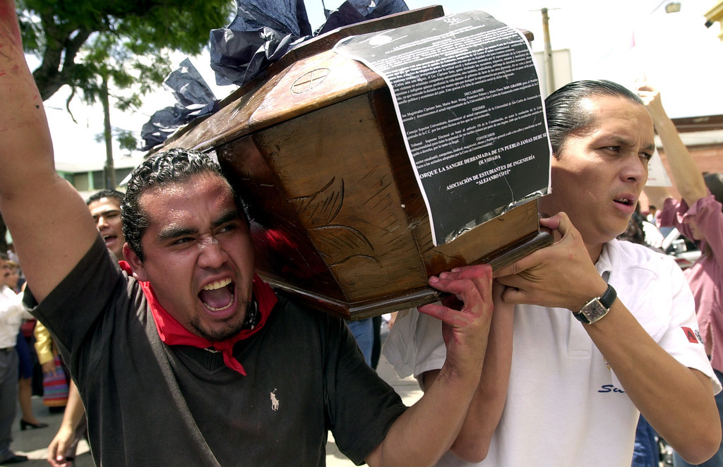 . Protesters carry a coffin that symbolizes the death of Guatemala\'s Constitutional Court in front of the  Electoral Supreme Tribunal in Guatemala City on Wednesday, July 16, 2003.  More than 30 social organizations condemned the country\'s highest court for clearing the way for former dictor Efrain Rios Montt to run for president in the November 2003 elections. (AP Photo/ Rodrigo Abd)