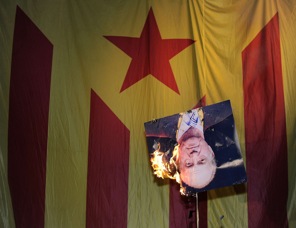. A picture of Spain\'s King Juan Carlos burns after a member of radical left-wing Catalan independentist political party CUP (Popular Unity Candidates) sets its fire in front of an Independentist flag in Barcelona, on September 11, 2013. Independence-seeking Catalans marshalled their forces today to make a human link they say will stretch across 86 cities, towns and villages along the coast of the northeastern region on the Mediterranean, passing landmarks such as the Sagrada Familia basilica in Barcelona and the city\'s Camp Nou football stadium. JOSEP LAGO/AFP/Getty Images