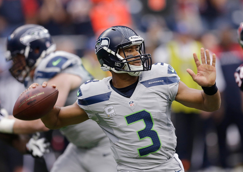 . Seattle Seahawks\' Russell Wilson throws against the Houston Texans during the first quarter an NFL football game Sunday, Sept. 29, 2013, in Houston. (AP Photo/David J. Phillip)