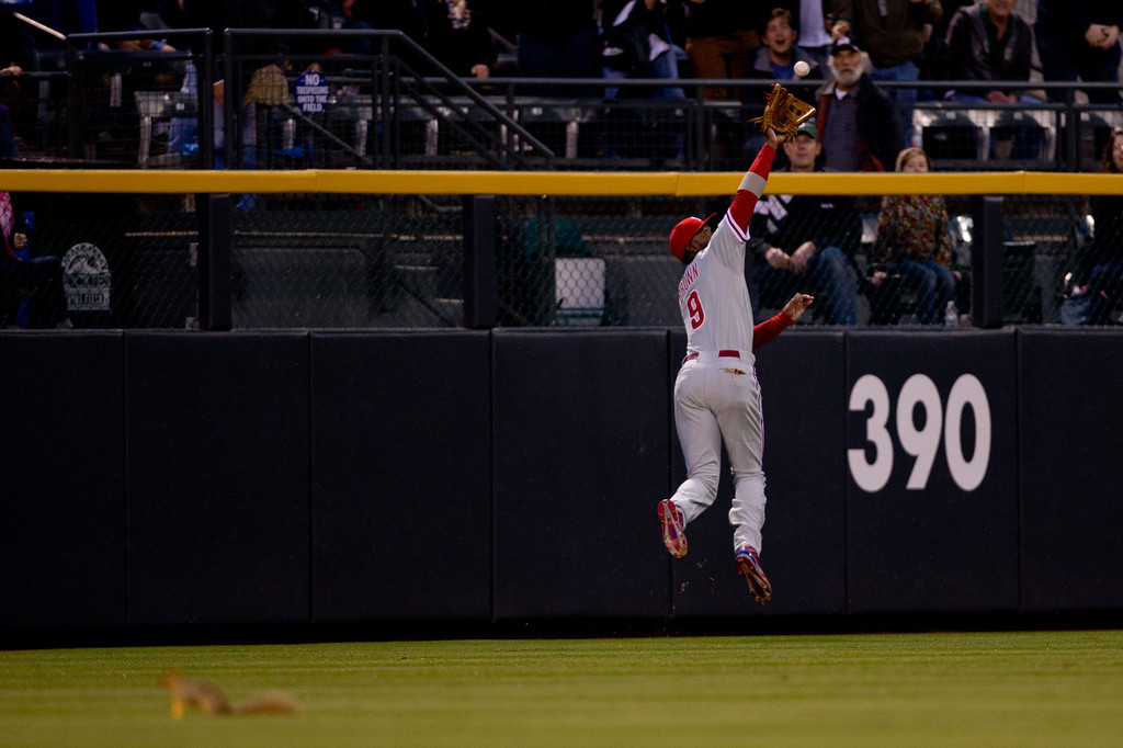 . Left fielder Domonic Brown #9 of the Philadelphia Phillies makes a leaping catch at the warning track on a ball off the bat of Troy Tulowitzki #2 of the Colorado Rockies for the first out of the fourth inning at Coors Field on April 19, 2014 in Denver, Colorado.  (Photo by Justin Edmonds/Getty Images)