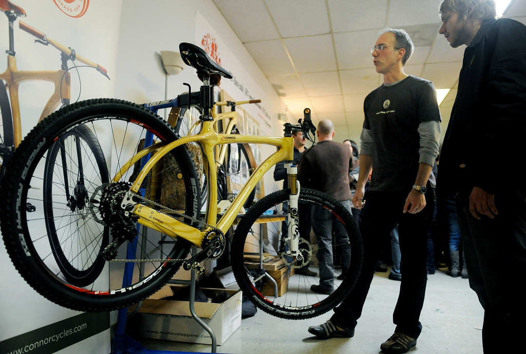 . Chris Connor, owner of Connor Wood Bicycles, second from right, talks to an interested spectator on Dec. 6 during the Holiday Mancraft 2013 craft fair at the VFW Post in Denver, Colo. Connor said his bikes range from $3,500 to $13,000 depending on their design, and that one of his mountain bikes finished the Leadville 100, a legendary mountain bike race through Colorado. Photo by Jamie Cotten, Special to The Denver Post