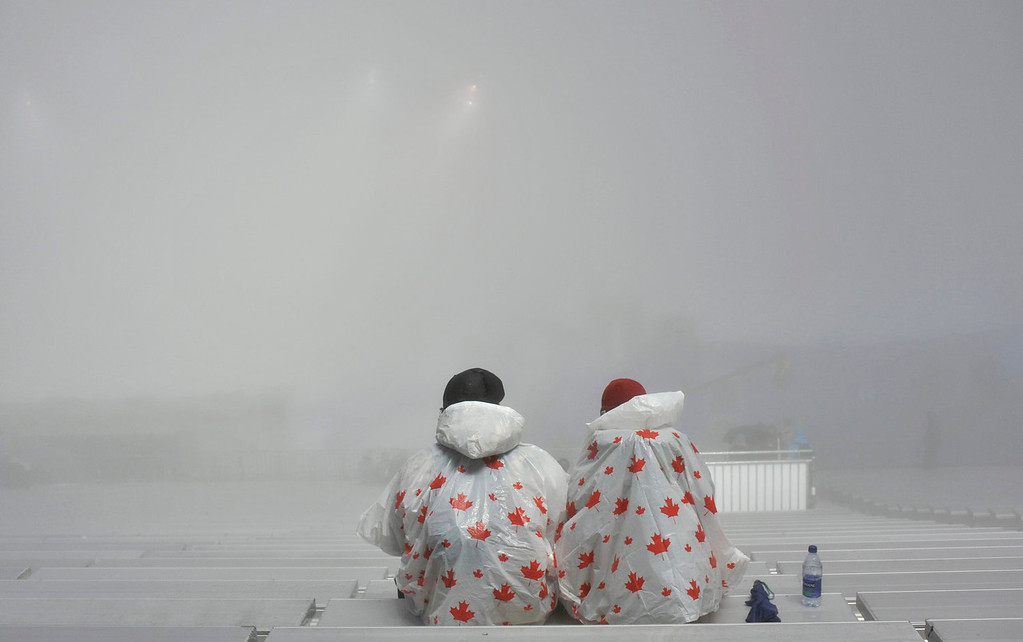 . Spectators waits in the fog prior to the women\'s snowboard cross on Cypress Mountain at the Vancouver 2010 Olympics in Vancouver, British Columbia, Tuesday, Feb. 16, 2010. (AP Photo/Bela Szandelszky)
