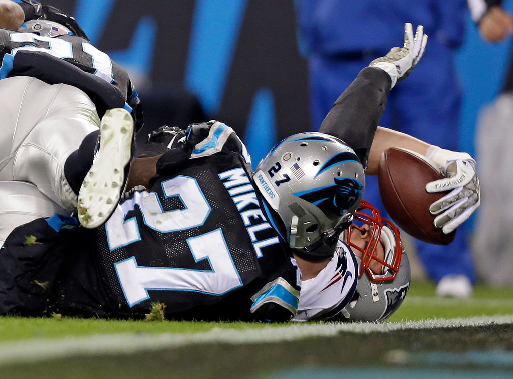 . New England Patriots\' Rob Gronkowski, right, stretches the ball over the goal line for a touchdown as Carolina Panthers\' Quintin Mikell, left, defends during the second half of an NFL football game in Charlotte, N.C., Monday, Nov. 18, 2013. (AP Photo/Gerry Broome)