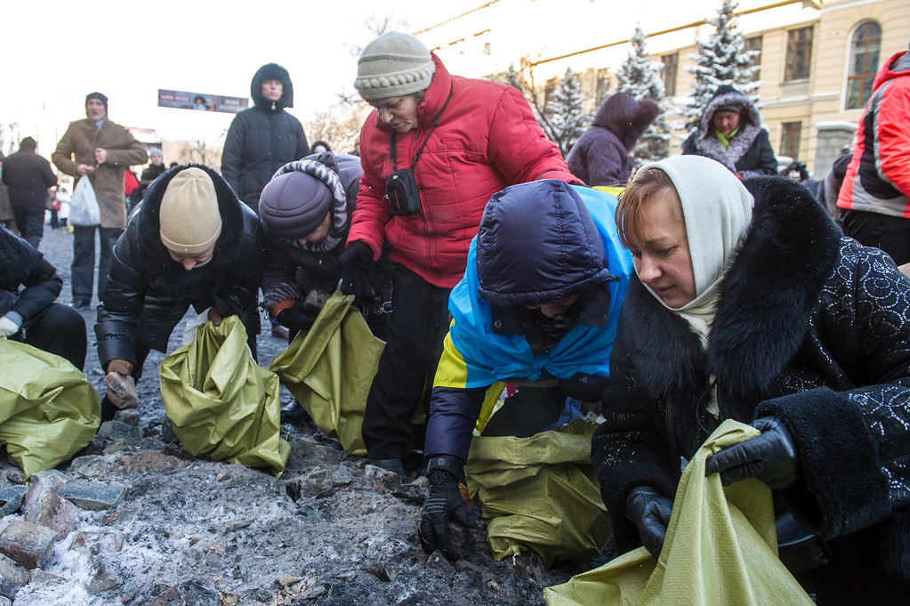 . Ukrainian women collect stones from the site of clashes between pro-EU protesters and riot police in central Kiev on January 23, 2014.  AFP PHOTO/VOLODYMYR SHUVAYEV/AFP/Getty Images