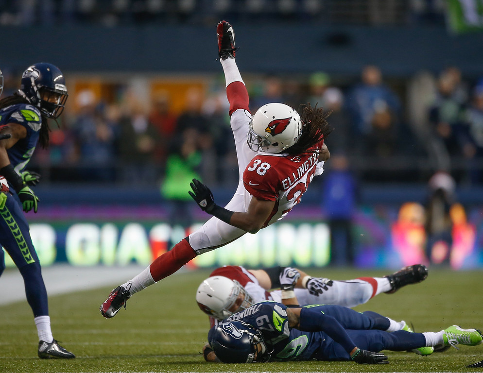. Running back Andre Ellington #38 of the Arizona Cardinals is tackled against the Seattle Seahawks at CenturyLink Field on December 22, 2013 in Seattle, Washington. The Cardinals defeated the Seahawks 17-10.  (Photo by Otto Greule Jr/Getty Images)