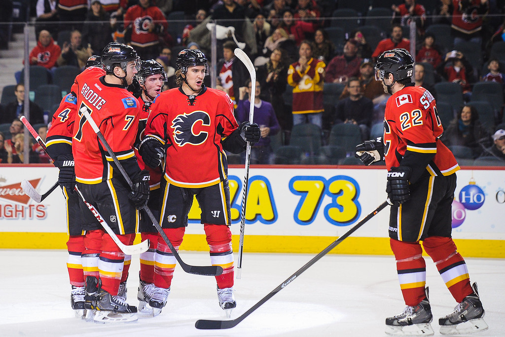 . CALGARY, AB - DECEMBER 6: (L to R) Kris Russell #4, T.J. Brodie #7, Sven Baertschi #47, Mikael Backlund #11, and Lee Stempniak #22 of the Calgary Flames celebrate after Kris Russell scored the team\'s first goal against the Colorado Avalanche during an NHL game at Scotiabank Saddledome on December 6, 2013 in Calgary, Alberta, Canada. (Photo by Derek Leung/Getty Images)