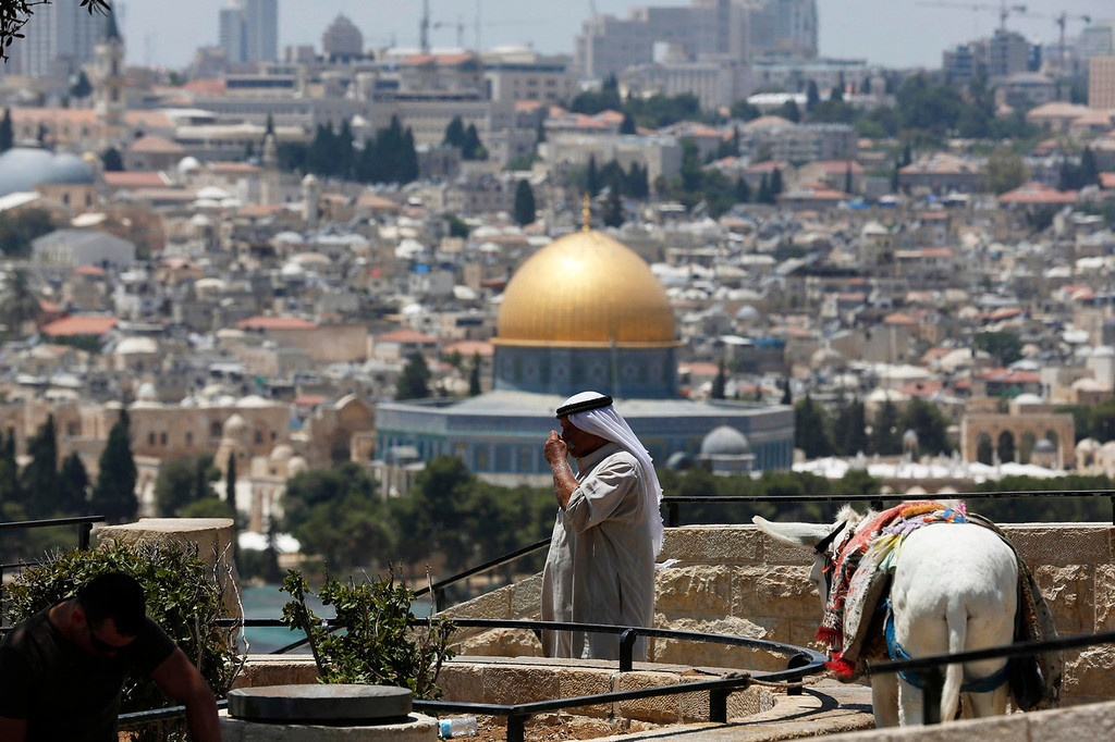 . A Palestinian who sells donkey rides to tourists stands at a lookout point on the Mount of Olives as the Dome of the Rock on the compound known to Muslims as al-Haram al-Sharif, and to Jews as Temple Mount, is seen in the background July 24, 2013. Israeli and Palestinian officials put forward clashing formats for peace talks due to resume in Washington on Monday for the first time in nearly three years after intense U.S. mediation. It is unclear how the United States hopes to bridge the core issues in the dispute, including borders, the future of Jewish settlements on the West Bank, the fate of Palestinian refugees and the status of Jerusalem. Picture taken July 24, 2013. REUTERS/Baz Ratner (JERUSALEM - Tags: POLITICS ANIMALS)