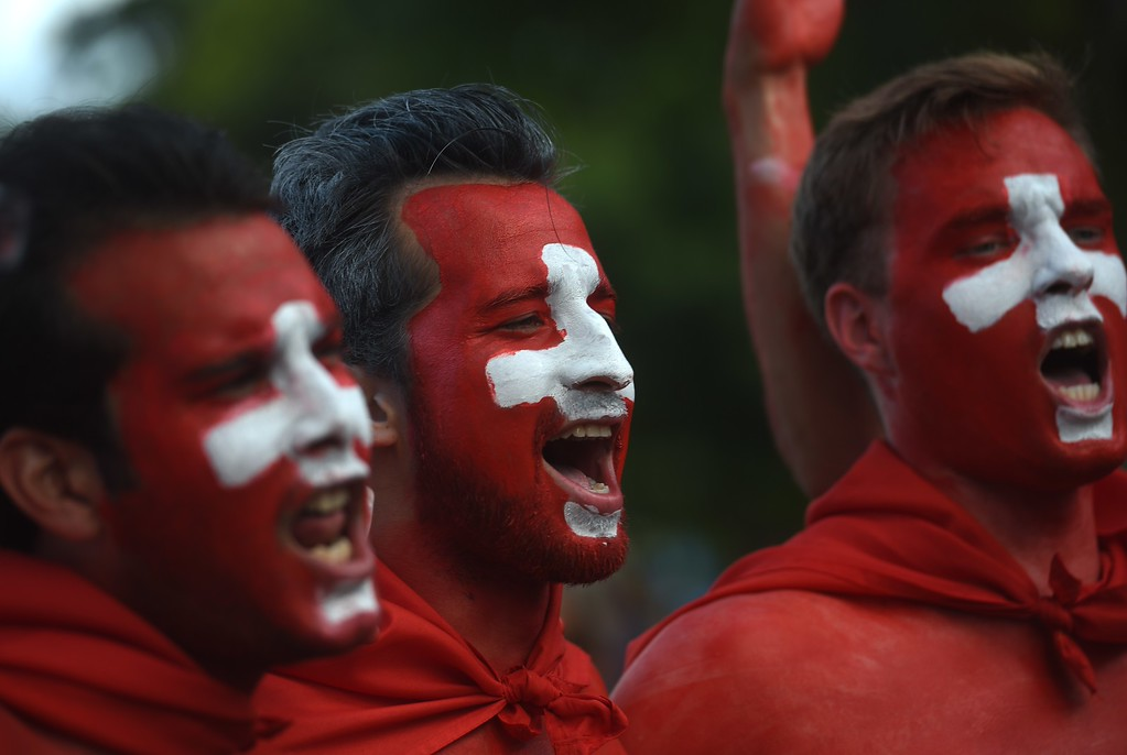 . Switzerland supporters with their faces painted in the colors of their national flag sing as they arrive for the Group E football match between Switzerland and France at the Fonte Nova Arena in Salvador during the 2014 FIFA World Cup on June 20, 2014. AFP PHOTO / DIMITAR  DILKOFF/AFP/Getty Images