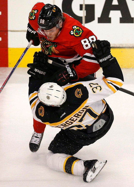 . Chicago Blackhawks\' Patrick Kane (88) checks Boston Bruins\' Patrice Bergeron during the first period in Game 1 of their NHL Stanley Cup Finals hockey game in Chicago, Illinois, June 12, 2013. REUTERS/Jim Young