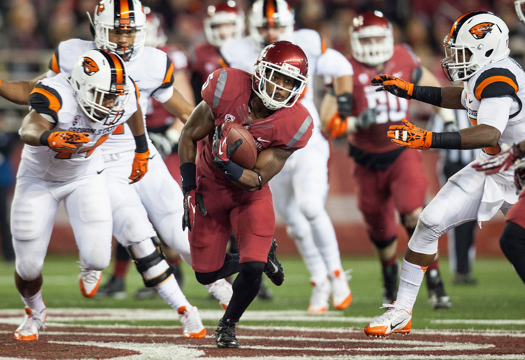 . Washington State wide receiver Rickey Galvin, center, attempts to avoid Oregon State safety Ryan Murphy, right, after catching a Connor Halliday pass during the first quarter of an NCAA college football game Saturday, Oct. 12, 2013, at Martin Stadium in Pullman, Wash. (AP Photo/Dean Hare)
