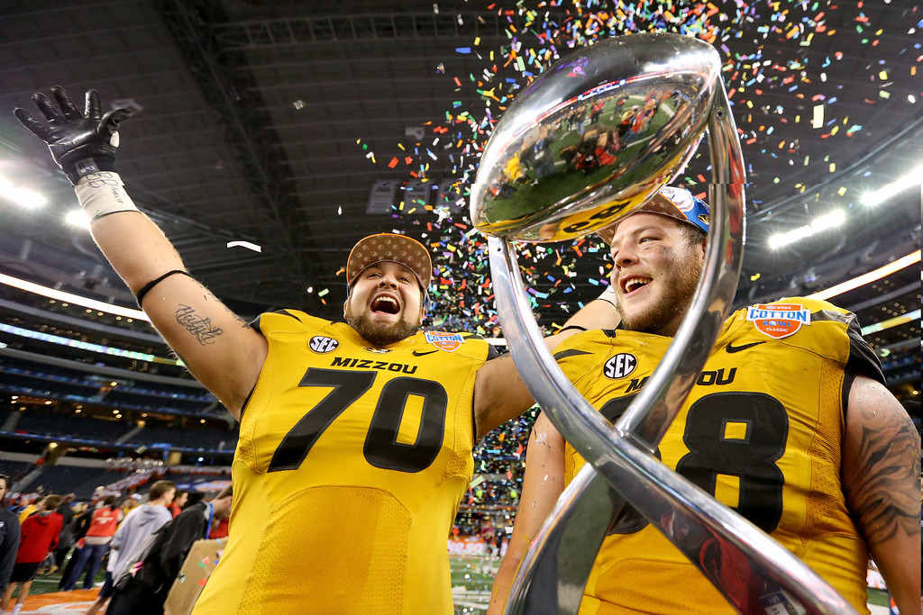 . ARLINGTON, TX - JANUARY 03:  Anthony Gatti #70 and Justin Britt #68 of the Missouri Tigers celebrate after the Tigers defeat the Oklahoma State Cowboys 41-31 during the AT&T Cotton Bowl on January 3, 2014 in Arlington, Texas.  (Photo by Ronald Martinez/Getty Images)