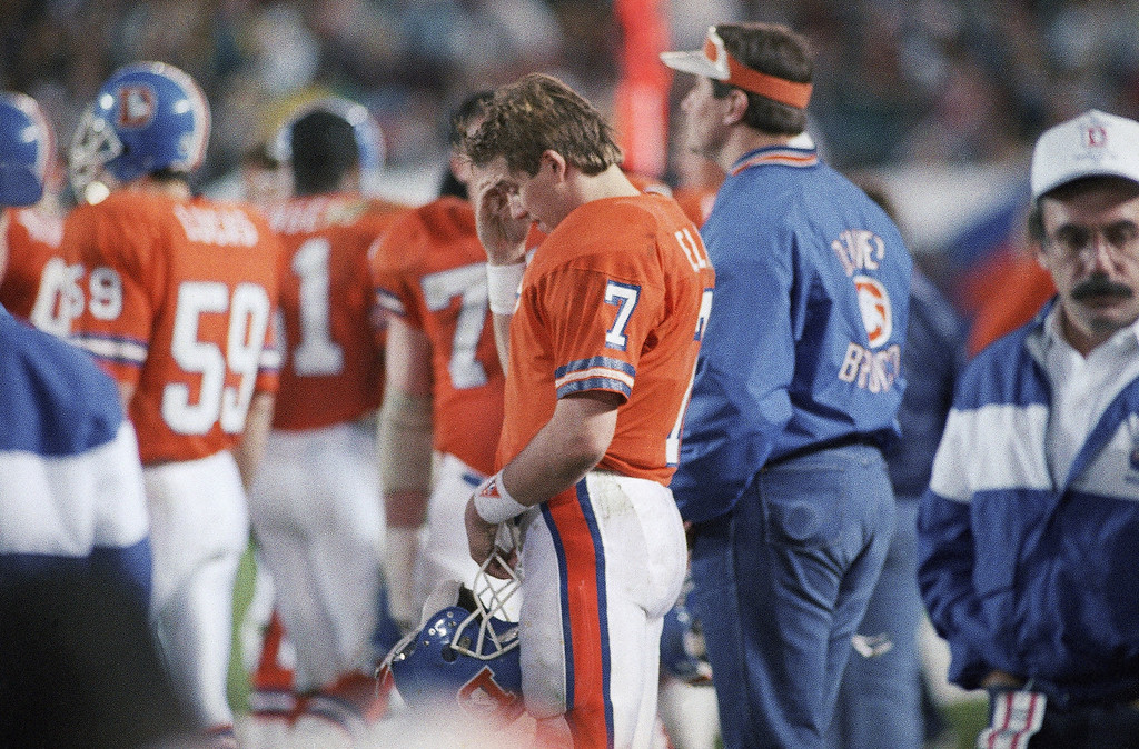 . Denver Broncos quarterback John Elway stands dejected on the sidelines during final two minutes of Super Bowl game with Washington Redskins, Sunday, Jan. 31, 1988 in San Diego. Elway was sacked 5 times for 50 yards and was held to 14 completions in 38 attempts. Redskins won, 42-10. (AP Photo/Ed Andrieski)