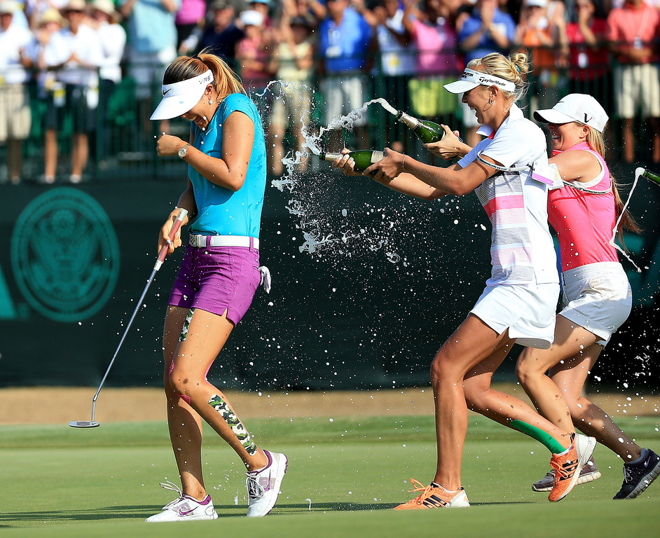 . Michelle Wie of the USA is drenched with champagne by Jessica Korda (centre) and Jamie Kuhn after holing the winning putt at the par 3, 17th hole during the final round of the 69th U.S. Women\'s Open at Pinehurst Resort & Country Club, Course No. 2, on June 22, 2014 in Pinehurst, North Carolina.  (Photo by David Cannon/Getty Images)