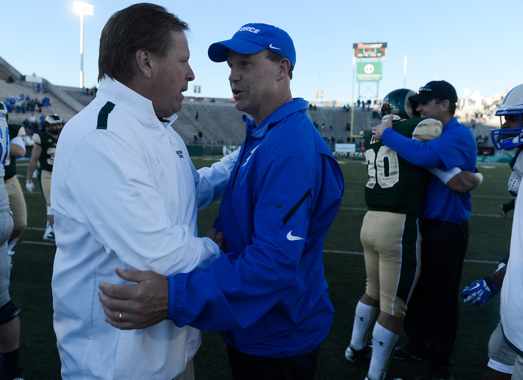 . Colorado State head coach, Jim McElwain, left, talks with Air Force head coach, Troy Calhoun, at center field after Colorado State defeated the Falcons 58-13. Saturday afternoon, November 30, 2013. (Photo By Andy Cross/The Denver Post)