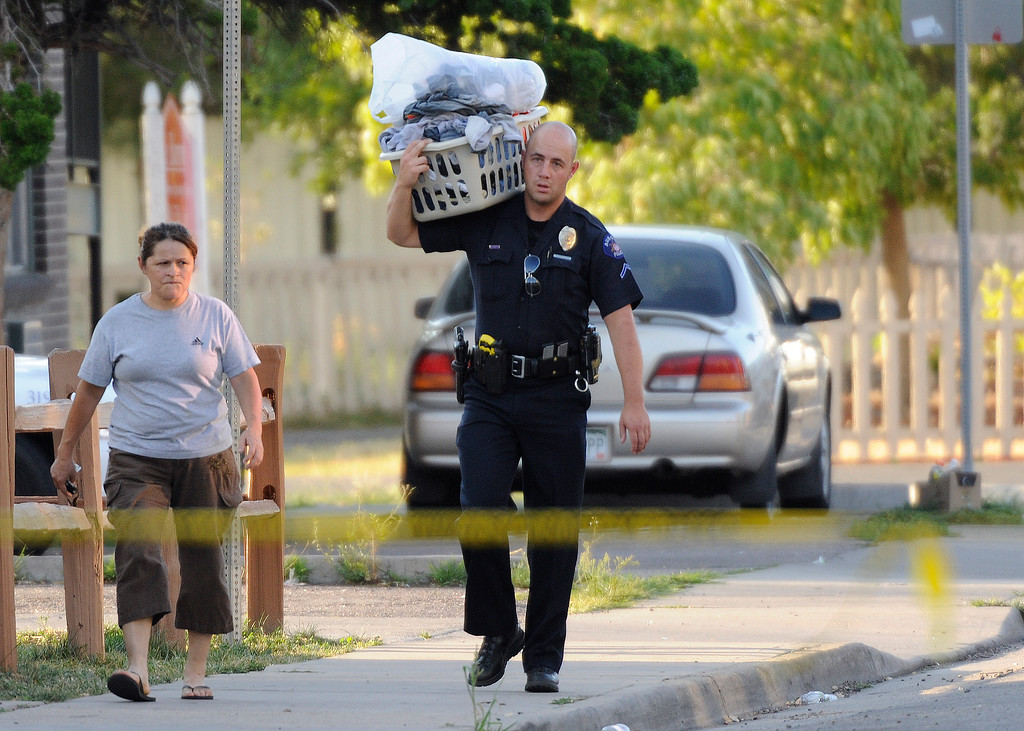 . Aurora Police Officer Campagna carries a laundry basket for a resident that got to return for a few minutes to her home. Residents of neighboring apartments got to return to collect items from their homes that had been evacuated because of the bobby trapped home of shooting suspect James Holmes in Aurora on Friday, July 20, 2012.    Cyrus McCrimmon, The  Denver Post